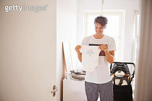Mid adult man in nursery holding baby clothes - gettyimageskorea