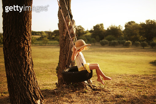 A 6 years old girl swinging in the countryside of south of France - gettyimageskorea