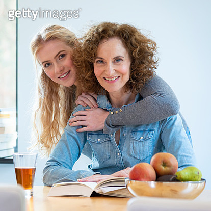 Mother and daughter drinking hot tea and reading book, indoors, looking at the camera - gettyimageskorea