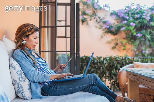 Woman using laptop and mobile phone on outdoor veranda - gettyimageskorea