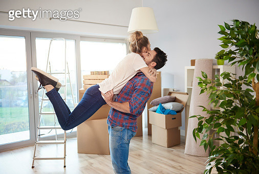 Young couple at home, surrounded by cardboard boxes, man lifting woman in excited hug - gettyimageskorea