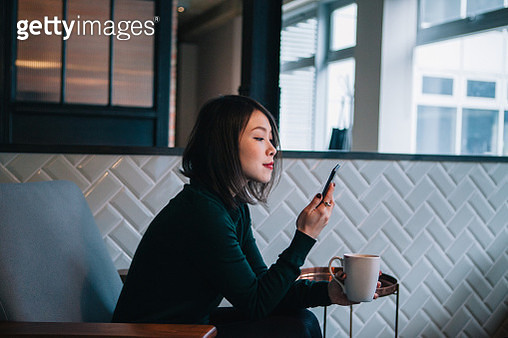 Portrait of young confident young businesswoman in a loft style work environment. Mixed race female staff of a tech startup. She is wearing smart casuals. - gettyimageskorea