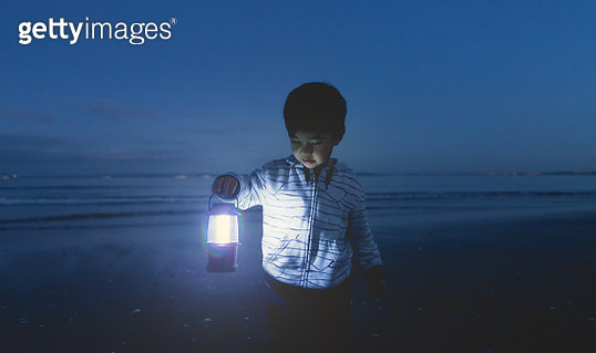 Boy with the lamp in his hand searching what he lost. - gettyimageskorea