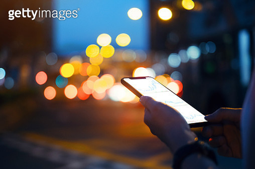 Close up of hands checking financial trading data on smartphone in city street at night - gettyimageskorea