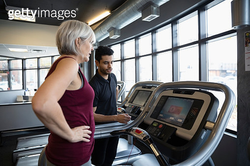 Personal trainer guiding senior woman on treadmill in gym - gettyimageskorea