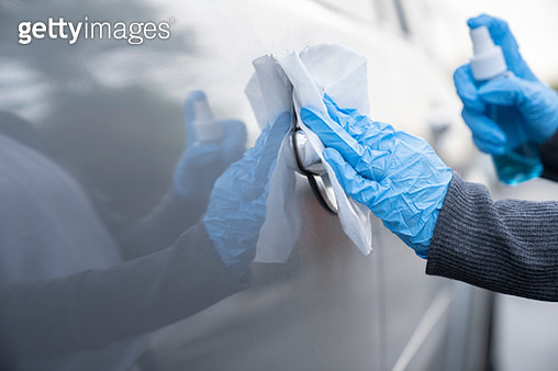 Hands wearing gloves and washing car door by alcohol spray - gettyimageskorea