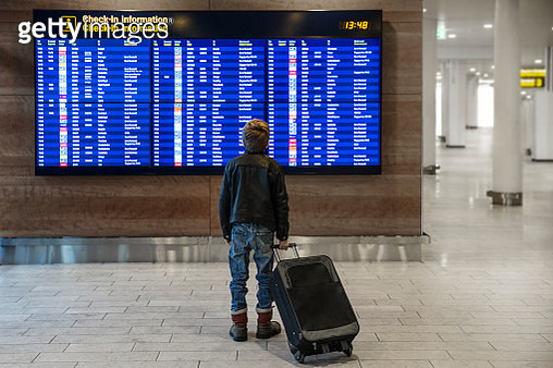 Rear view of boy with wheeled suitcase looking at airport departure board - gettyimageskorea