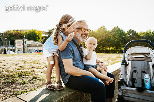Two kids having fun and playing with their grandpa while out at the park together. - gettyimageskorea