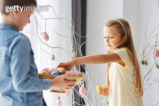 Girl and brother decorating twigs with colourful easter eggs - gettyimageskorea
