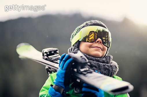 Little boy aged 9 is carrying skis on winter day. Nikon D850 - gettyimageskorea