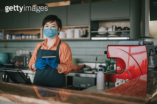 an asian chinese small business owner with face mask and protective gloves hand over the dessert to her customer at kitchen counter smiling looking at camera - gettyimageskorea