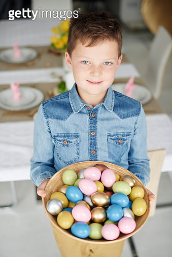 Portrait of boy holding bowl of colourful easter eggs - gettyimageskorea
