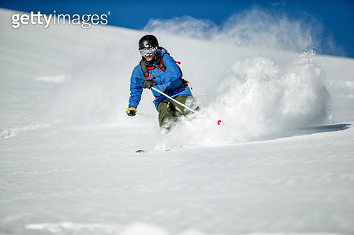 Guy skiing fresh snow on a sunny day. - gettyimageskorea
