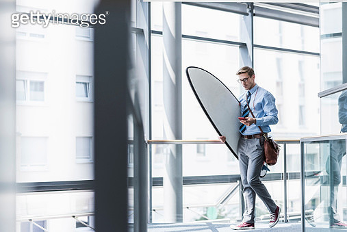 Businessman with cell phone carrying surfboard in office - gettyimageskorea
