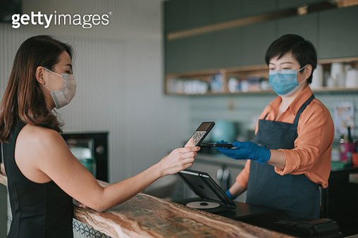 an asian chinese cafe owner businesswoman receiving payment from her customer at counter using QR code contactless payment - gettyimageskorea