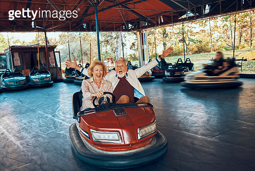 playful senior couple having fun together driving bumper car - gettyimageskorea