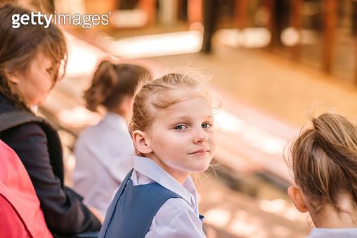 Portrait of cute girl with friends outside school - gettyimageskorea