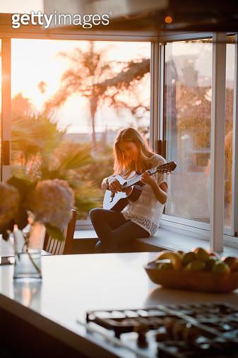woman in window playing guitar - gettyimageskorea