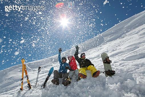 Friends throwing snow sat on ski slope - gettyimageskorea