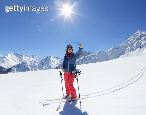 Woman taking photo on ski slope - gettyimageskorea