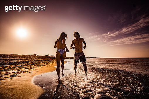 Young couple having fun while running through water on the beach at sunrise. Copy space. - gettyimageskorea
