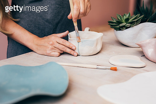 Midsection Of Woman Painting Pitcher At Desk - gettyimageskorea