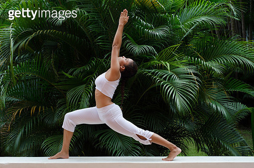 A woman doing a yoga pose on a garden - gettyimageskorea
