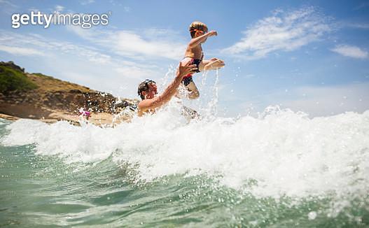 Man throwing son into ocean wave, Calvi, Corsica, France - gettyimageskorea