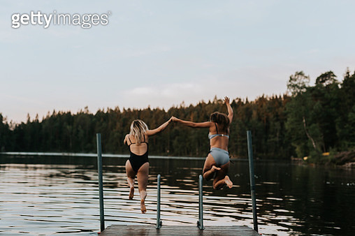 Women jumping together into water - gettyimageskorea