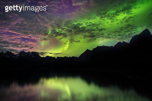 Aurora Borealis above mountain ranges, Narsaq, Vestgronland, Greenland - gettyimageskorea