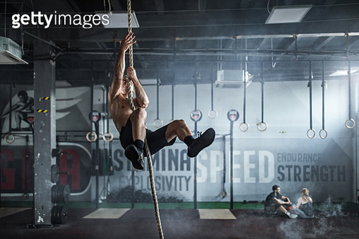 Young athletic man exercising strength on a rope in a gym. - gettyimageskorea