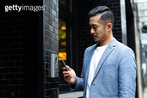young chinese man using mobile phone unlock door ,smart home - gettyimageskorea