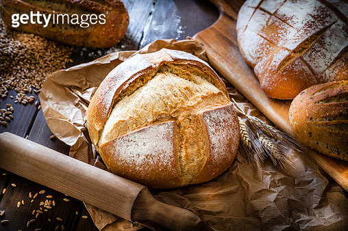 Different types of bread shot on rustic wooden table. A fresh baked loaf of bread is on foreground on a brown craft paper. Predominant color is brown. Low key DSRL studio photo taken with Canon EOS 5D Mk II and Canon EF 100mm f/2.8L Macro IS USM - gettyimageskorea