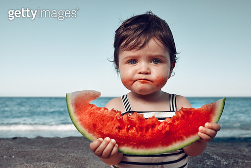 funny little girl on the beach eating watermelon and making funny face. - gettyimageskorea