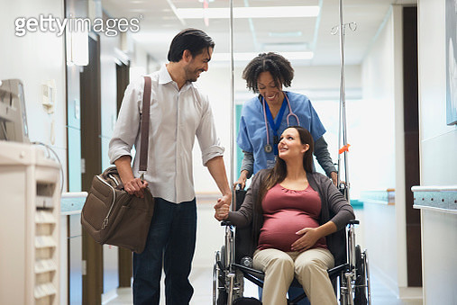 Pregnant woman on wheelchair in hospital with husband - gettyimageskorea