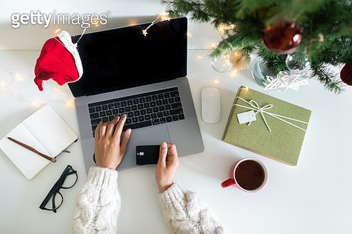 Woman using credit card to shop online for Christmas present. - gettyimageskorea