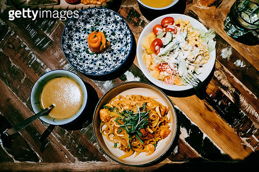 Directly above view of smoked salmon appetizer, soup, salad and seafood pasta freshly served on table to share in restaurant - gettyimageskorea