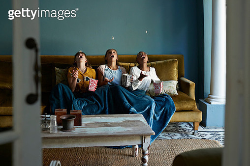 Tween girls hanging out and eating popcorn together in bohemian style home - gettyimageskorea