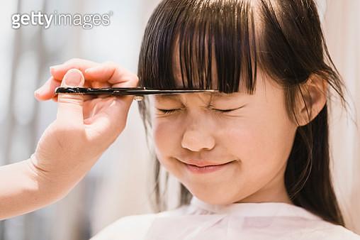 Asian girl having her forelock cut by beautician. - gettyimageskorea