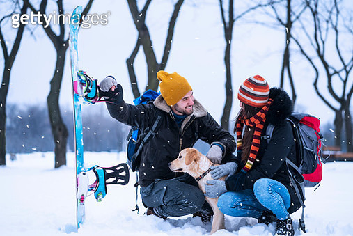 Young couple enjoying winter with dogs - gettyimageskorea