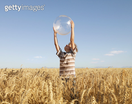 Boy holding clear globe in field - gettyimageskorea