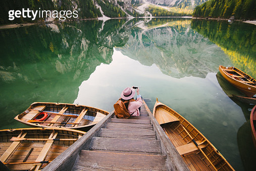 Woman relaxing on pier, Lago di Braies, Dolomite Alps, Val di Braies, South Tyrol, Italy - gettyimageskorea