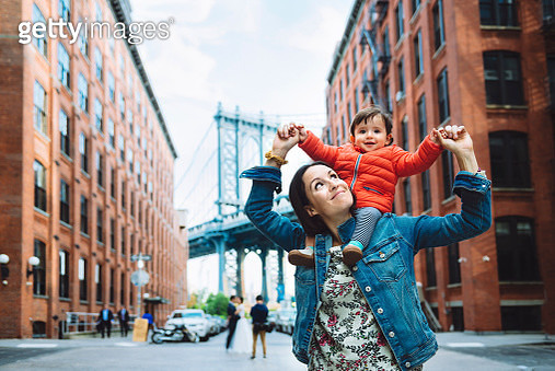 USA, New York, New York City, Mother and baby in Brooklyn with Manhattan Bridge in the background - gettyimageskorea