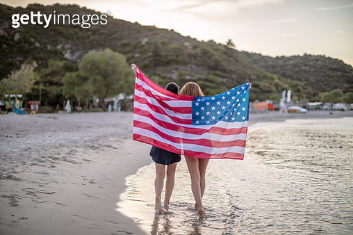Young Women Wrapped in American Flag on a Beach - gettyimageskorea