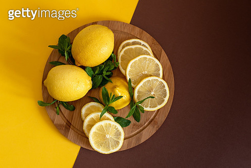 Board with cut lemons and zest on wooden table, closeup - gettyimageskorea