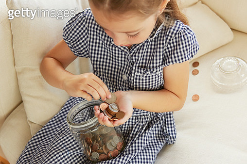 Young girl, sitting on sofa, counting money from jar, elevated view - gettyimageskorea
