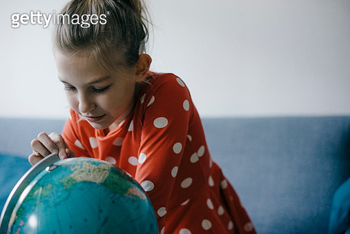 Girl at home looking at globe - gettyimageskorea