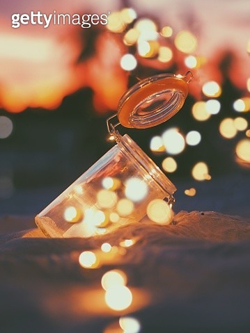 Close-Up Of Illuminated Christmas Lights With Jar On Sand During Sunset - gettyimageskorea