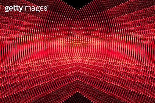 Close-up abstract pattern of intertwined colorful light beams of color red color in movement on a black background. - gettyimageskorea