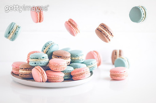 Chocolate, vanilla and strawberry macaroons on a plate and mid air - gettyimageskorea